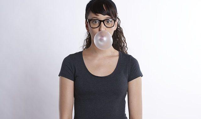 meitene ar brillēm burbuļgumija košļājamā gumija